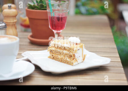 The piece of cake on table of summer terrace in cafe, picnic, set table - Stock Photo