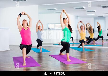 Four girls practicing yoga, , Virabhadrasana / Warrior pose - Stock Photo