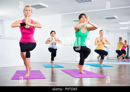 woman practicing yoga garudasana eagle pose mature