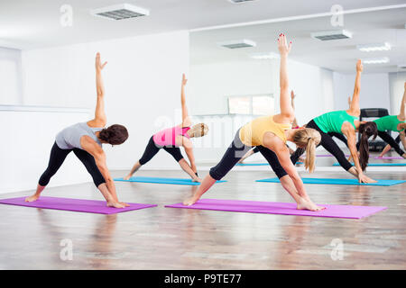 Four girls practicing yoga,Trikonasana / Bikram triangle right - Stock Photo