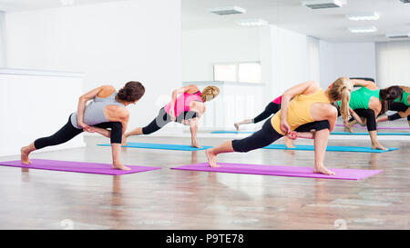 Four girls practicing yoga - Stock Photo