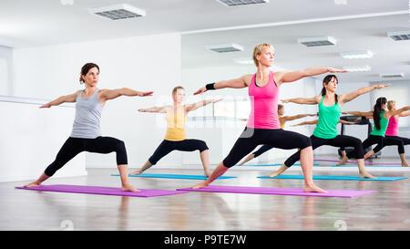 Four girls practicing yoga, Virabhadrasana / Warrior pose - Stock Photo