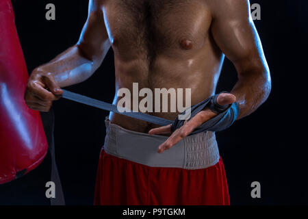 Close-up view on male hands of young athlete tying gray boxing bandages. Boxer man getting ready for hard kickboxing training session in gym. Black ba - Stock Photo