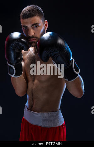 Double arm block. Boxing trainer showing defensive techniques. Combat sport, fight club. Studio shot on a black background - Stock Photo