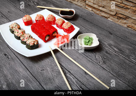 Japanese cuisine. On the table of the restaurant are beautifully laid out a set of rolls, sauce, ginger and wasabi. - Stock Photo