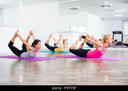 Three girls practicing yoga, Dhanurasana / Bow pose - Stock Photo