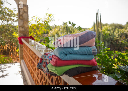 a pile of folded towels ready for a beach outing rest on a terrace wall with garden in sunlight in background - Stock Photo