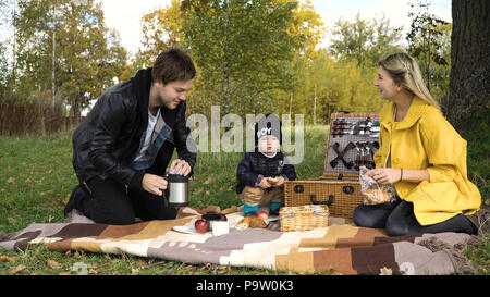 Young family with son at a picnic in the park on a sunny day.Family having picnic outdoors.Cute family picnicking in the park. - Stock Photo