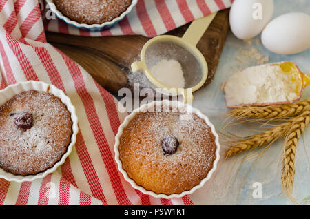 Cakes with cerries on a table in small porcelain cups .There are  eggs, flour, wheat, powdered sugar next to cakes. - Stock Photo