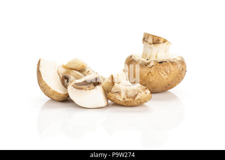 Sliced brown champignons one whole and three slices isolated on white background fresh raw mushrooms - Stock Photo