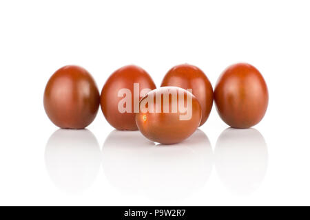 Black red grape cherry tomatoes isolated on white background four in row and one in front - Stock Photo