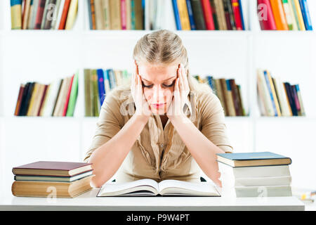 Young woman learning in library, she is tired - Stock Photo