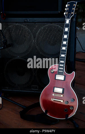 Electric guitar used for rock concerts, the instrument resting on stage near an acoustic box Stock Photo
