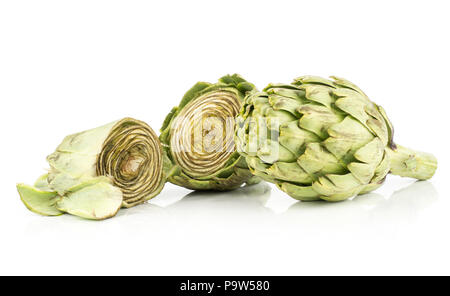 Two globe artichoke flowers one cut in two halves isolated on white background raw fresh cut - Stock Photo