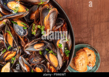 A full skillet of marinara mussels, shot from above on a dark rustic background with bread and a place for text - Stock Photo