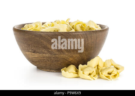 Raw Italian tortellini pasta in a wooden bowl isolated on white background traditional dumplings - Stock Photo