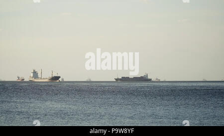 Cargo ships in the Bay of Manila. Large container ship in the sea, blue sky and clouds. Philippines, Manila. - Stock Photo