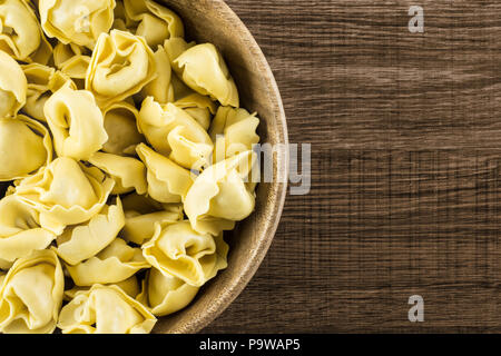 Raw tortellini pasta in a wooden bowl flatlay on brown wood background Italian traditional dumpling - Stock Photo
