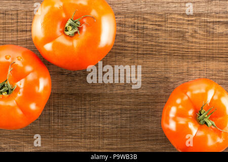 Three red tomato top view isolated on brown wood background - Stock Photo