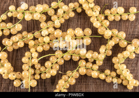 Lot of whole fresh white currant berry blanka variety flatlay on brown wood - Stock Photo