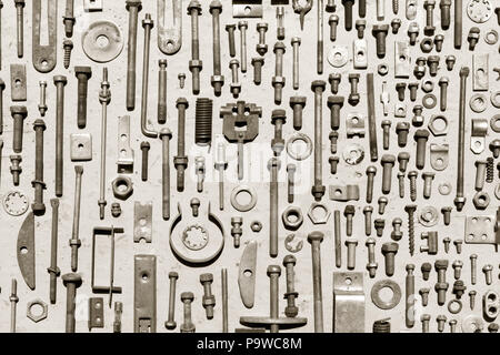 set of old rusty metal screws, nuts and bolts on a gray background. black and white photo. Flat lay, top view - Stock Photo