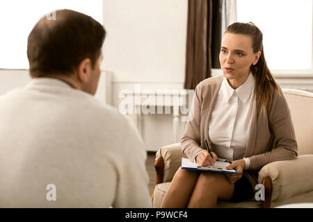 During a psychological session. Professional friendly smart psychologist looking at her patient and asking him a question while taking notes - Stock Photo