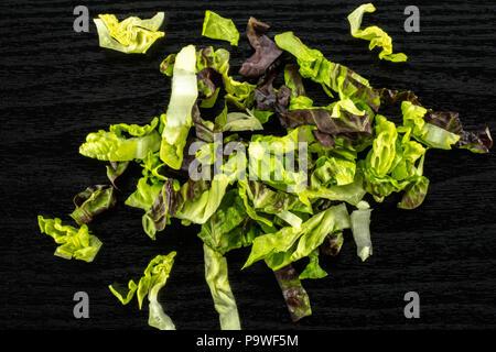 Fresh green lettuce red little gem variety chopped flatlay on black wood - Stock Photo