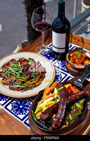 Sausages and Beef carpaccio with potatoes served in Mexican restaurant, red wine - Stock Photo