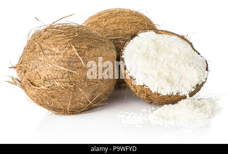 Two coconuts and one broken half filled with shavings isolated on white background brown fibrous shell with milk meat - Stock Photo