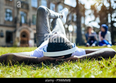 Relaxed man lying on grass and listening music - Stock Photo