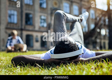 Joyful young man listening music while lying on grass - Stock Photo