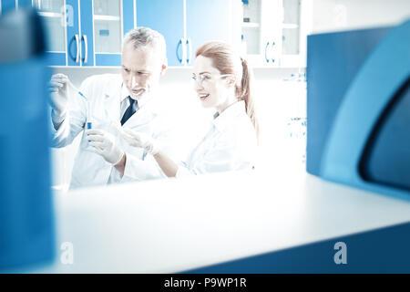 Joyful professional scientists conducting an experiment - Stock Photo