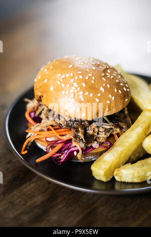 pulled pork and coleslaw salad burger sandwich with french fries snack meal - Stock Photo