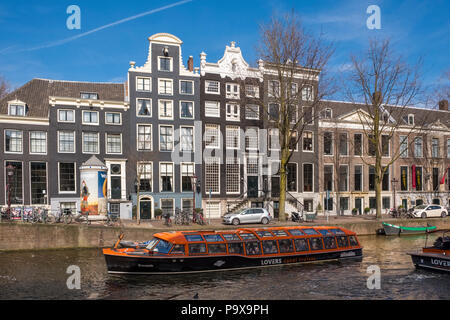 Sightseeing boat on a canal in Amsterdam, The Netherlands, Europe with traditional canal houses behind - Stock Photo