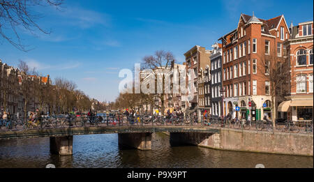 Many bicycles on a bridge overlooking a canal in Amsterdam, The Netherlands, Europe - Stock Photo