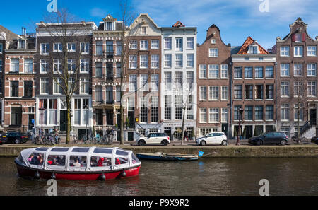 Tall narrow canal houses and a sightseeing tourist cruise boat on a canal in Amsterdam, The Netherlands, Europe - Stock Photo