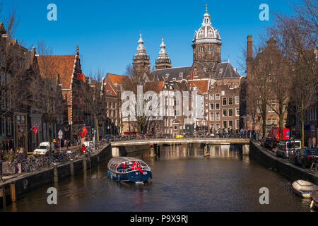 Many bicycles on a bridge overlooking a canal in Amsterdam, The Netherlands, Europe with a pleasure boat sailing underneath - Stock Photo