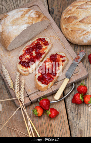 Strawberry jam on bread with wheat and strawberries on a wood background - Stock Photo