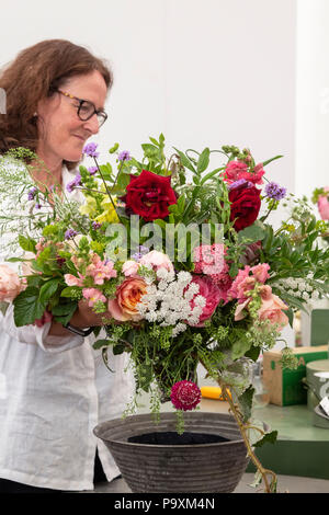Woman on a flower arranging stall with a bouquet of flowers at at RHS Hampton Court flower show 2018. London. UK - Stock Photo