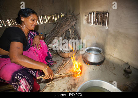 A villager woman in a remote subsistence farming village on an island in the Sundarbans, the Ganges Delta in Eastern India that is very vulnerable to sea level rise. She is cooking on a traditional clay oven, fueled by biofuel (rice stalks), low carbon cooking. - Stock Photo