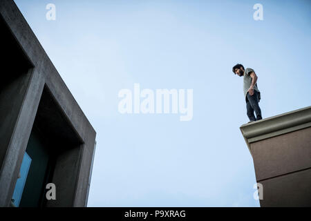 View from below of male parkour athlete standing on roof - Stock Photo