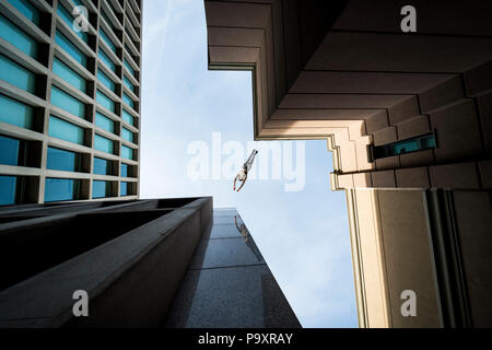 View from below of male parkour athlete jumping from one roof to another - Stock Photo