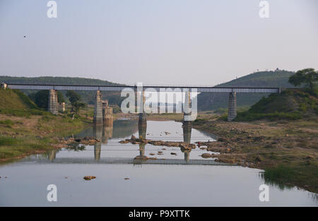 Landscape view of a narrow bridge stretching across a river creating a reflection. Photographed from a moving vehicle in India - Stock Photo