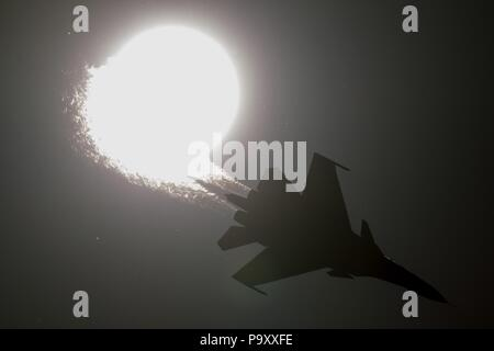 The Sukhoi Su-30SM twin-engine, supermaneuverable multirole jet fighter silhouettes against the Sun while performing its demonstration flight at the M - Stock Photo