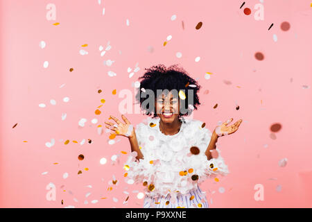 Celebrating happiness, young woman with big smile throwing confetti - Stock Photo