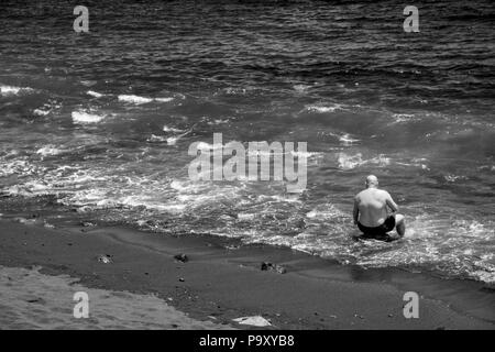 It has become evening and the beach at Playa Martianez, in Puerto de la Cruz, has been taught. This man on a stone and enjoys the rest. - Stock Photo