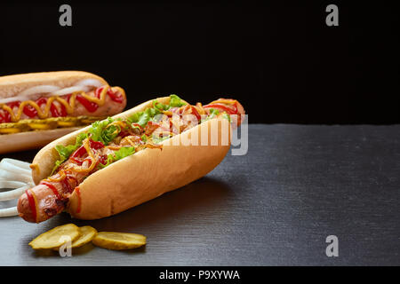 Two juicy hot dogs on dark slate background - Stock Photo