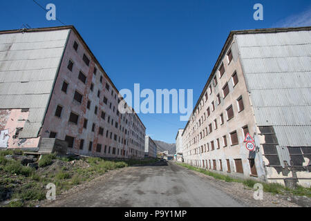 Rundown buildings and street in Provideniya, Russia - Stock Photo