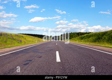 a wide road of asphalt built through a forest with different trees, sunny weather with a blue sky - Stock Photo