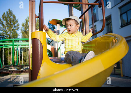 Nice cute boy of three years in a yellow jacket is playing on a bright playground. - Stock Photo